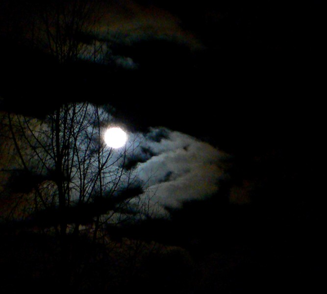 Full moon glaring through the clouds.