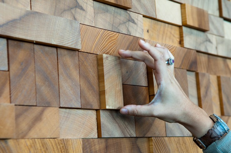 trying to grab a wood block out of the Vancouver Convention Center's Wall