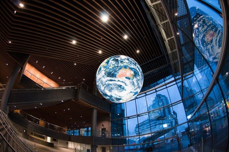 A lit globe of the Earth hangs from the ceiling of the IBC entrance after security, Vancouver Convention Center (west wing)